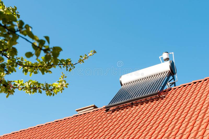 Solar water heater on rooftop. Green leaves, conceptual image of green house royalty free stock image