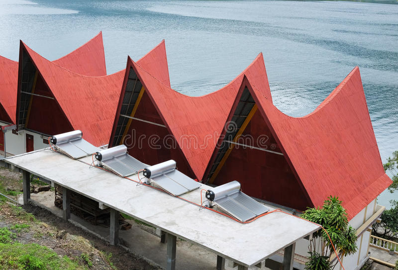 Solar water heaters and houses. Solar Water Heater supply electricity to batak-style houses with red roofs, Lake Toba, Indonesia stock images