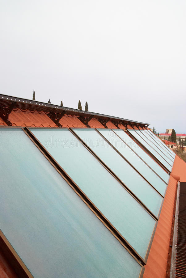 Solar water heating system. (geliosystem) on the red house roof royalty free stock images