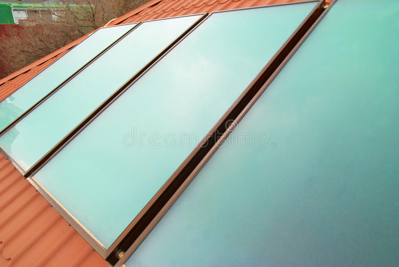 Solar water heating system. (geliosystem) on the red house roof royalty free stock photos