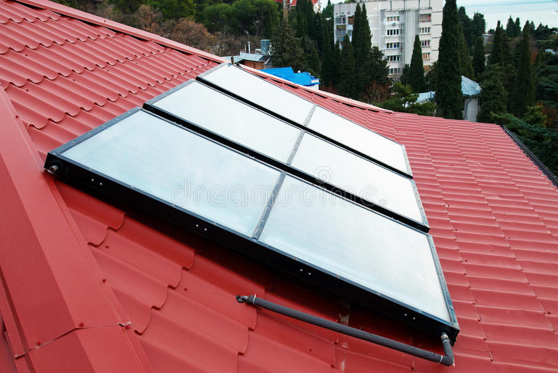 Solar water heating system. Solar water heating system (geliosystem) on the red house roof stock image