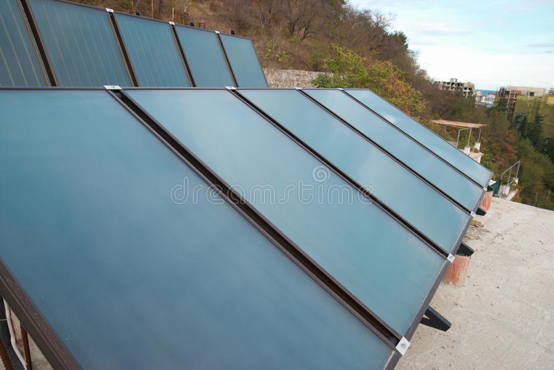 Solar water heating system. On the house roof royalty free stock photo