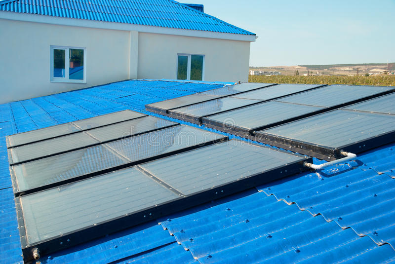 Solar water heating system. On the house roof royalty free stock images