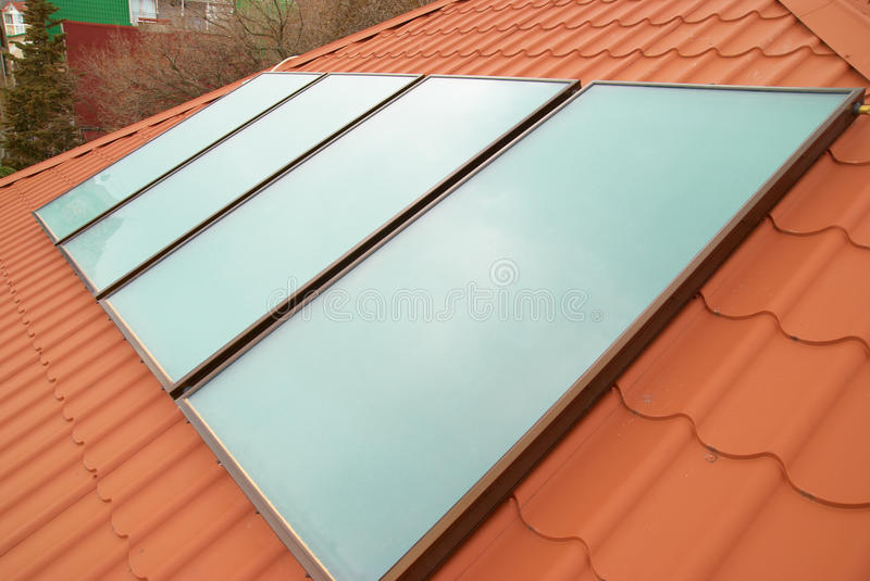 Solar water heating system. (geliosystem) on the red house roof royalty free stock photography