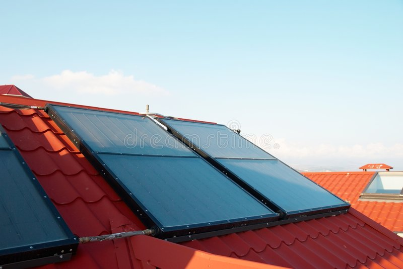 Solar water heating system. (geliosystem) on the red house roof royalty free stock image