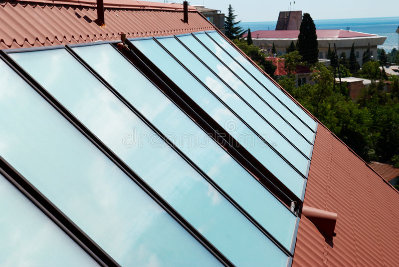 Solar water heating system. On the house roof royalty free stock photography