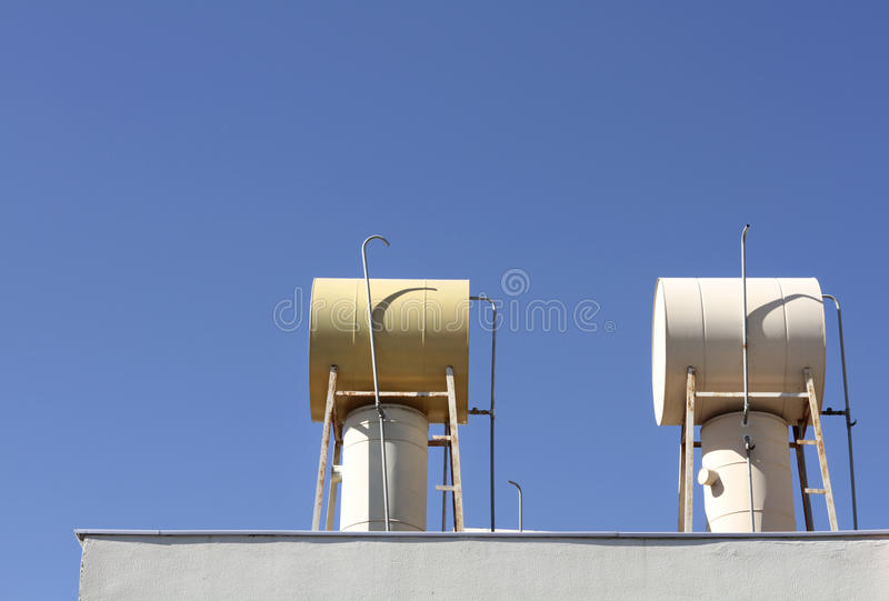 Solar Water Tanks On Rooftop. With Clean Blue Sky As Background royalty free stock photography