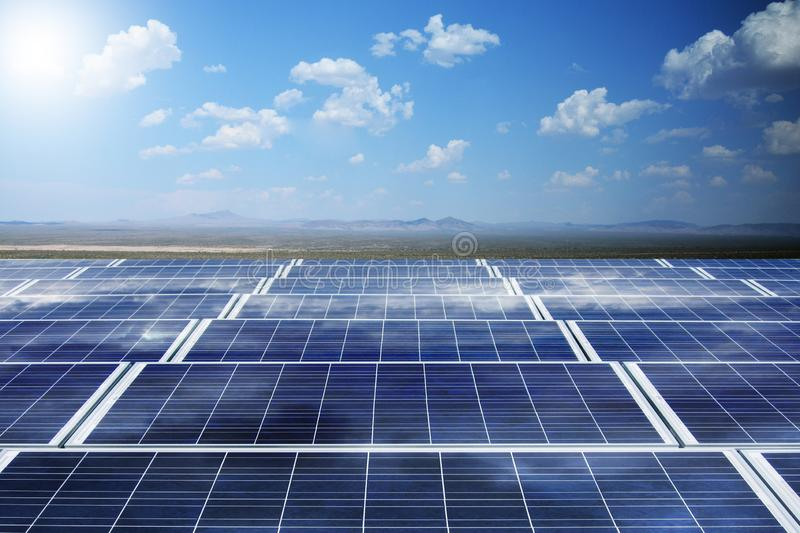 Solar and wind power with photovoltaic panels and wind turbine against blue sky producing renewable energy stock photo