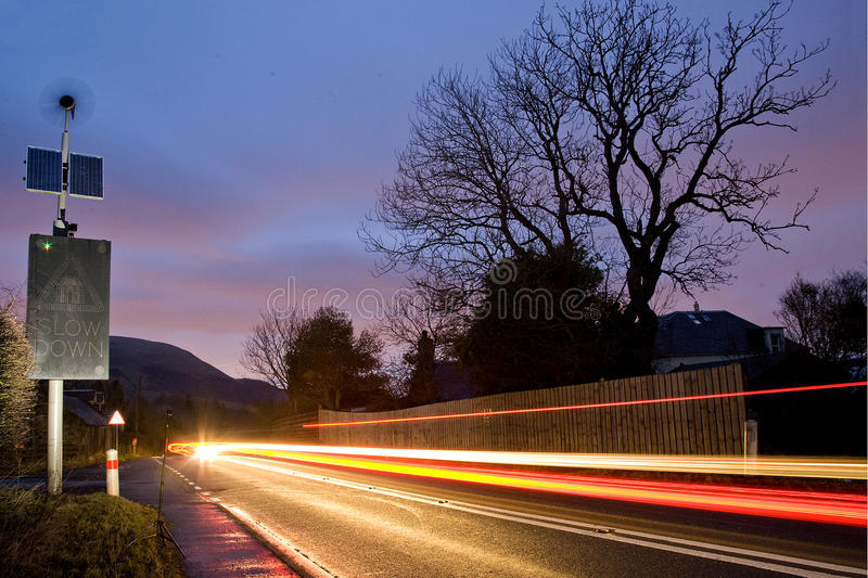Solar and wind powered road sign on road leading to Edinburgh, Scotland, UK at night stock image