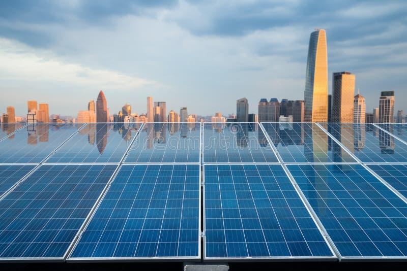 Solarenergieplatte mit Stadtdämmerung stockfotografie