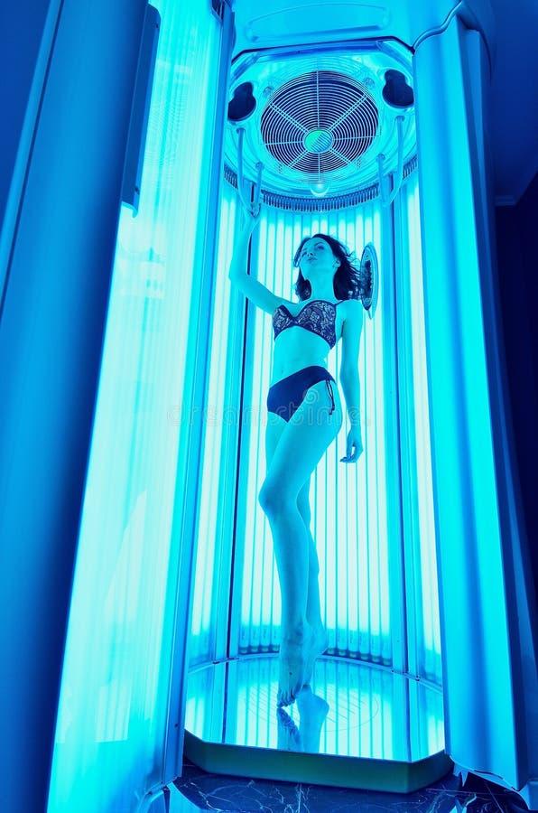 solarium Красивая маленькая девочка в бикини загорая в sunbed вертикальном стоковое изображение rf