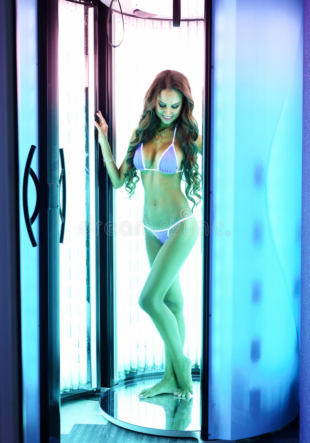 In solarium. woman with perfect body posing. In solarium. brunette with perfect body posing royalty free stock photography