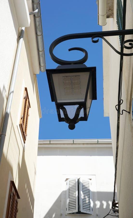 Solarstraßenlaterne von unterhalb entworfen wie die alte Weinleselampe auf der rustikalen Mittelmeerartfassade, Ansicht stockfotos