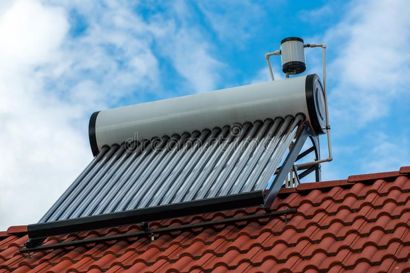 Solarwarmwasserbereiterkessel auf residentual Hausdachspitze, blauer Himmel mit weißen Wolken stockfoto