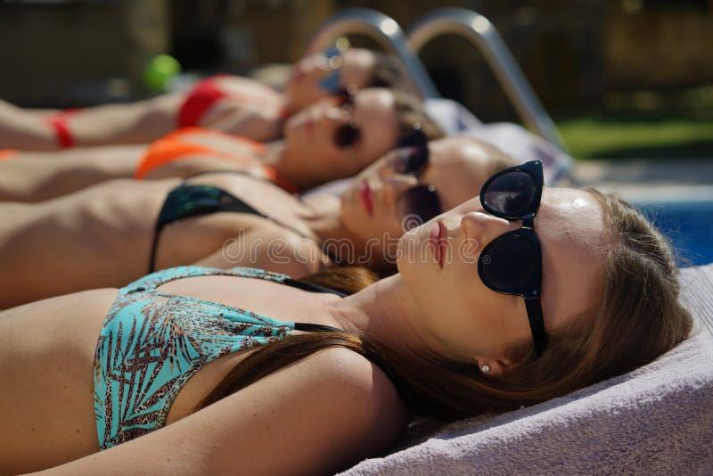 Solbada för fyra unga kvinnor arkivfoto