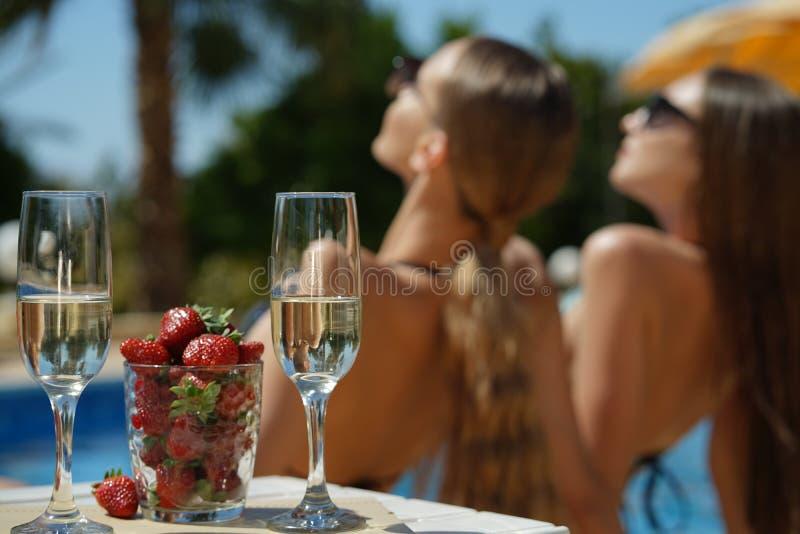 Solbada kvinnor, jordgubben och mousserande vin royaltyfria bilder