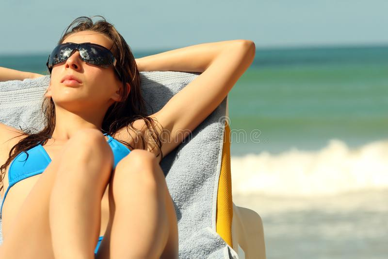 Solbada på stranden royaltyfria bilder