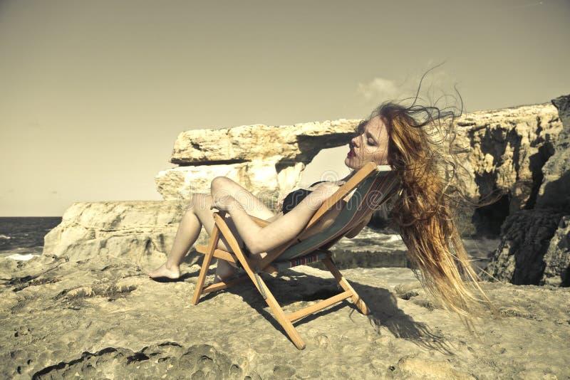 Solbada på stranden royaltyfri bild