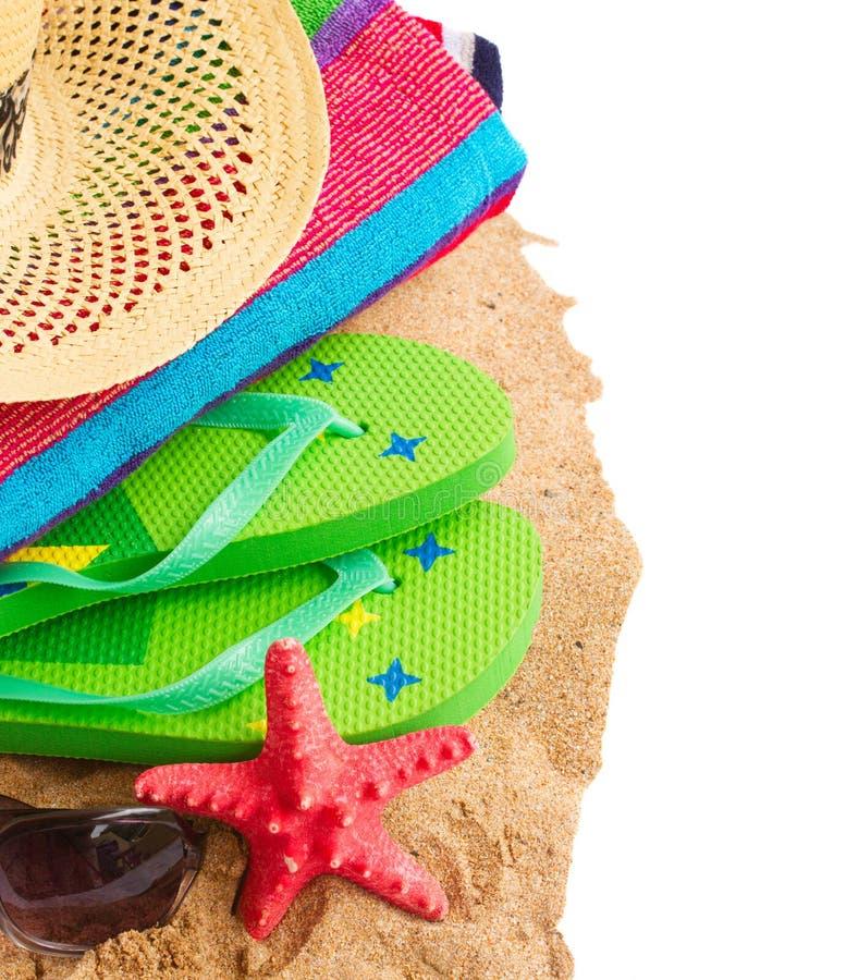 Solbada tillbehör och sugrörhatten på sand royaltyfria bilder