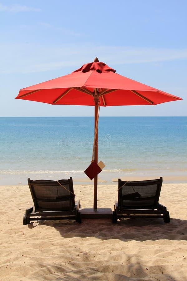 Solbada underlag med ett rött paraply royaltyfri fotografi