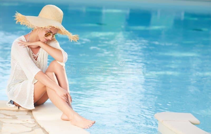 Solbadning för ung kvinna i simbassäng för brunnsortsemesterort royaltyfri bild