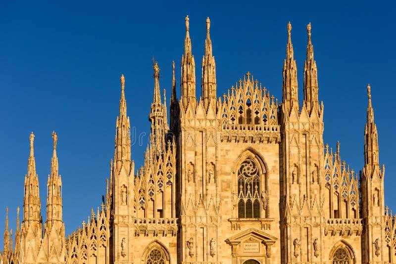 Solbelyst främre fasad av Duomodi Milano på skymning royaltyfri foto