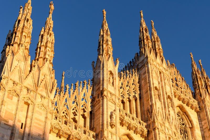 Solbelyst främre fasad av Duomodi Milano på skymning royaltyfria bilder