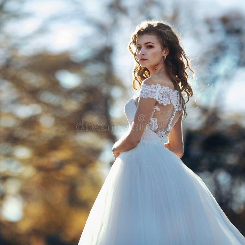 Solbelyst ursnygg brunettbrud i den vita klänningen som poserar i solnedgång f royaltyfri fotografi