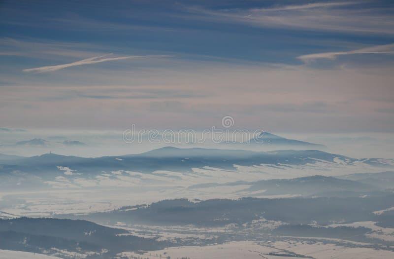 Solbelysta blåa kanter, dimmiga dalar under molnband i vinter royaltyfri foto