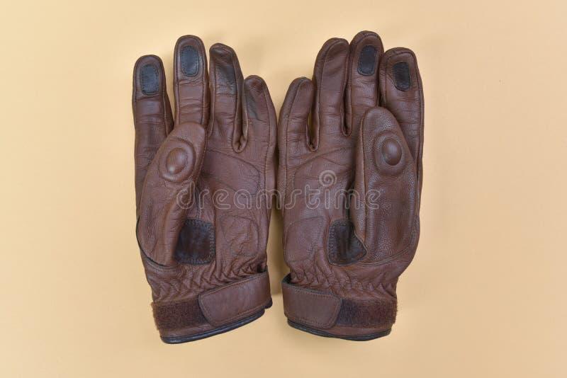 Solbrända bruna läderhandskar för att rida en motorcykel eller en cykel royaltyfri bild