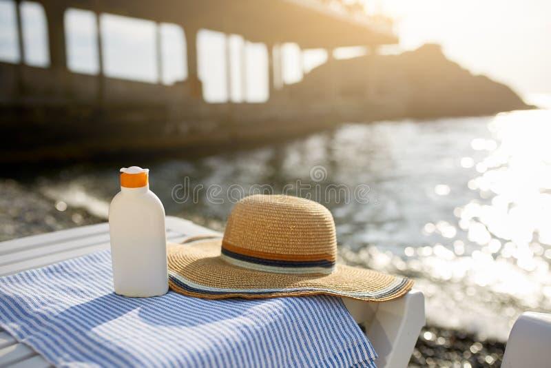 Solbrännakrämflaska på strandhandduken med havskusten på bakgrund Sunscreen på solstol utomhus på soluppgång eller solnedgång royaltyfria foton