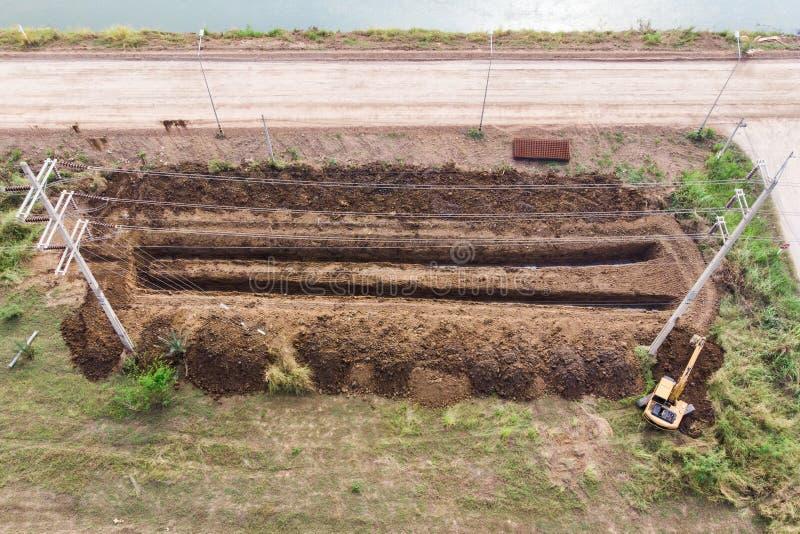 Solco di scavatura dell'escavatore a cucchiaia rovescia giallo su suolo nella zona agricola immagini stock libere da diritti