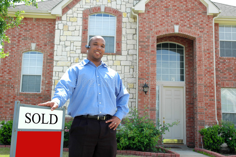 Sold. A real-estate agent stands outside a home with SOLD sign. Authorized to act as an agent for the sale of land stock photo