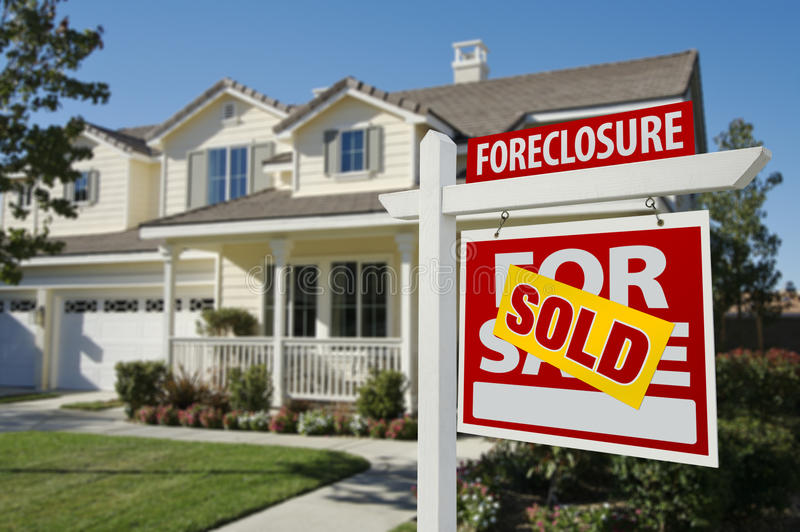 Sold Foreclosure Home For Sale Sign and House. Sold Foreclosure Home For Sale Sign in Front of Beautiful House royalty free stock image