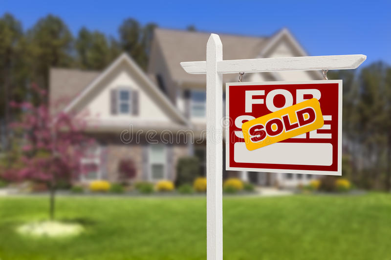 Sold Home For Sale Sign in Front of New House. Sold Home For Sale Real Estate Sign in Front of Beautiful New House royalty free stock photo
