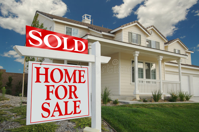Sold Home For Sale Sign & Home. Sold Home For Sale Sign in front of Beautiful New Home royalty free stock images