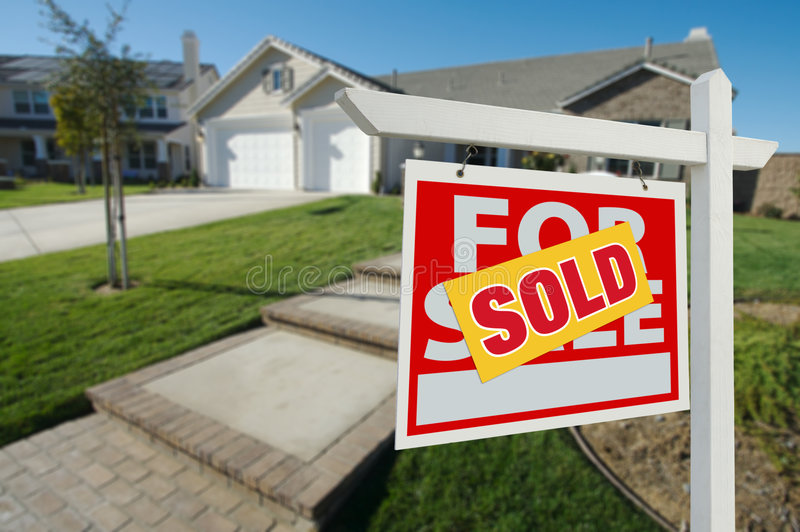 Sold Home For Sale Sign and House. Sold Home For Sale Sign in Front of New House royalty free stock images