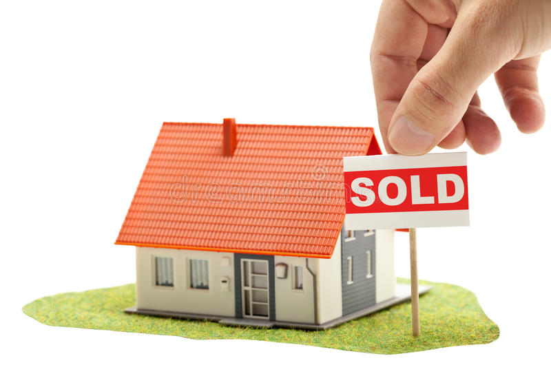 Sold house. Hand holding sold-sign in front of model house - real estate buying concept stock photo