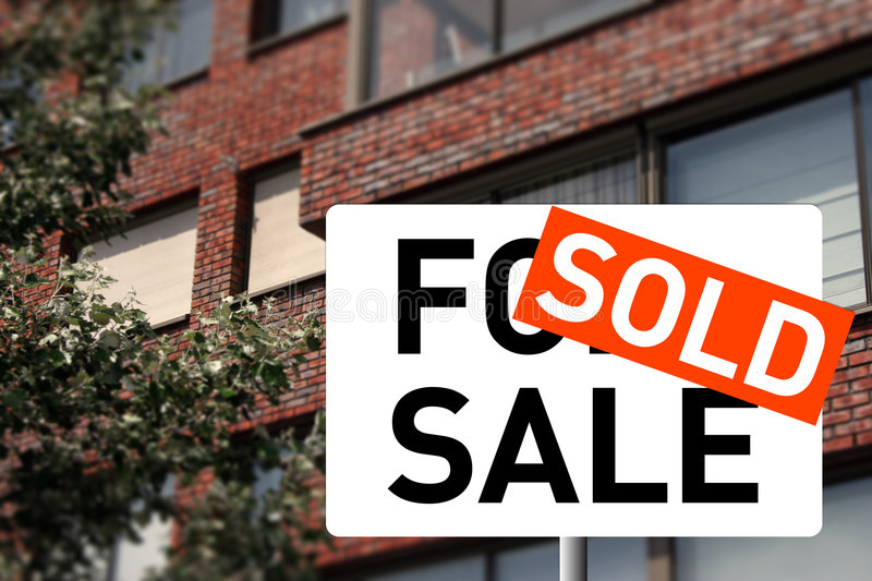 Sold house. A sold sign and a house on the background royalty free stock photography