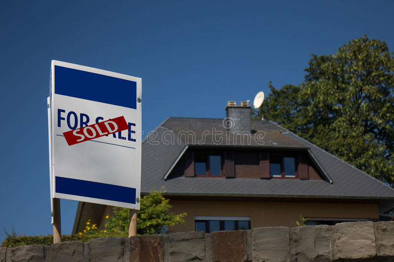 Sold house. Real estate listing sign with sold note in front of residential house for sale stock images