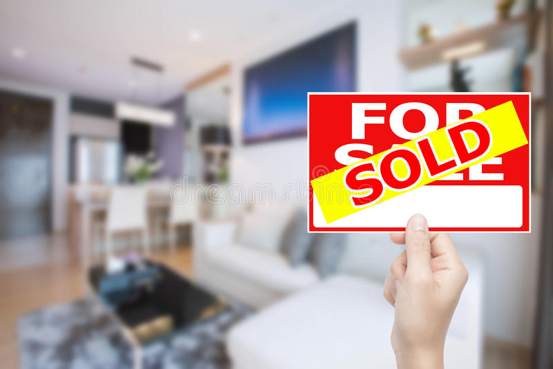 Sold house sign. Hand holding sold house sign stock photo