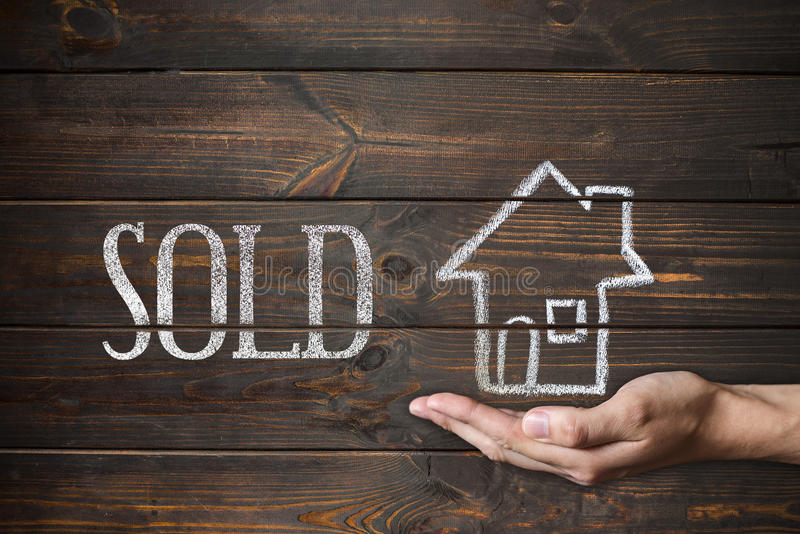 Sold house written on wooden boards. Drawing with chalk and male stock image