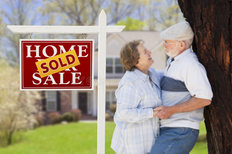 Sold Real Estate Sign with Senior Couple in Front of House. Sold Real Estate Sign with Happy Affectionate Senior Couple Hugging in Front of House stock image