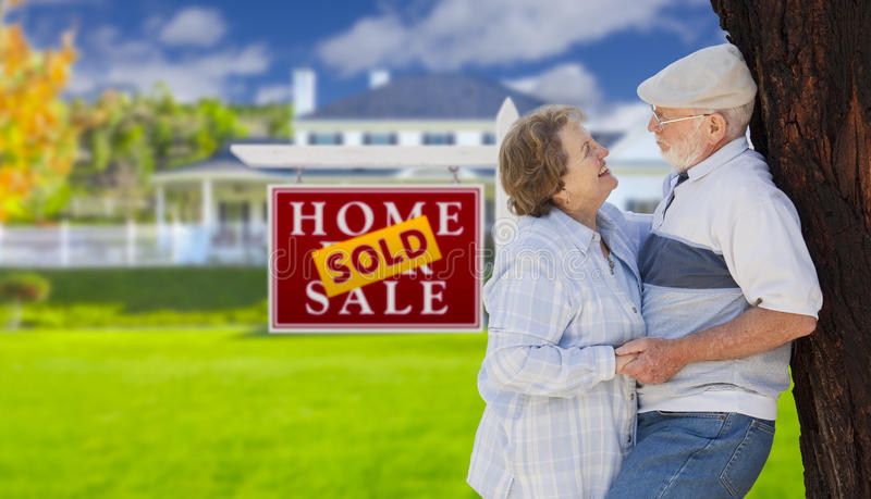 Sold Real Estate Sign with Senior Couple in Front of House. Sold Real Estate Sign with Happy Affectionate Senior Couple Hugging in Front of House stock photos