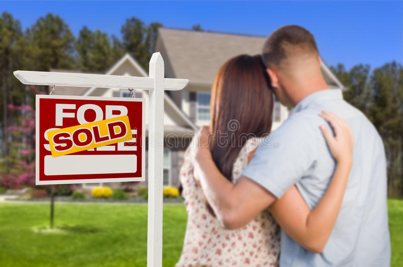 Sold For Sale Sign with Military Couple Looking at House. Sold For Sale Real Estate Sign and Affectionate Military Couple Looking at Nice New House stock photography