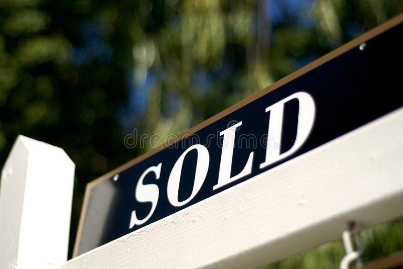 Sold sign in front of house or condo. Sold sign on white post in front of house, used by realtors, real estate agents, homeowners royalty free stock image