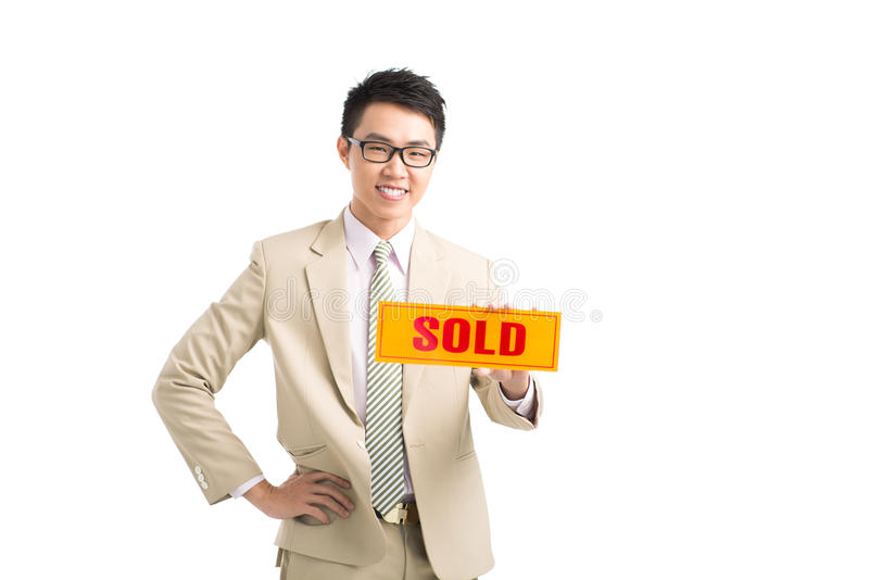 Sold signboard. Young Vietnamese broker holding sold signboard stock photos