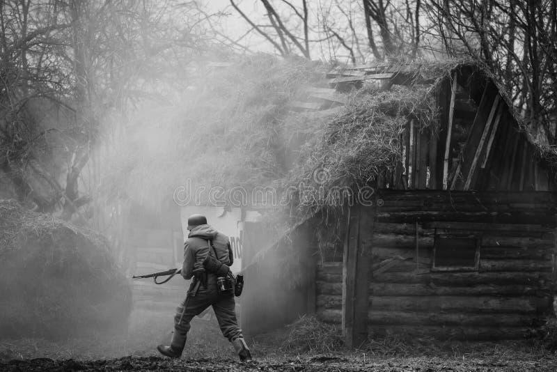 Soldado alemán In WW II de la infantería de Wehrmacht que corre en Battlefiel imagen de archivo