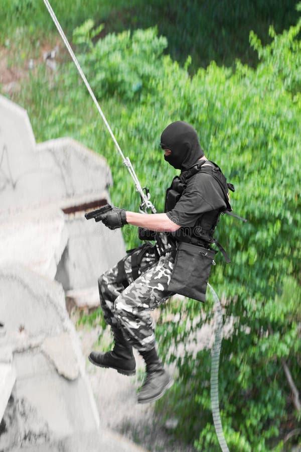 Soldado armado que rappelling com um injetor fotografia de stock royalty free