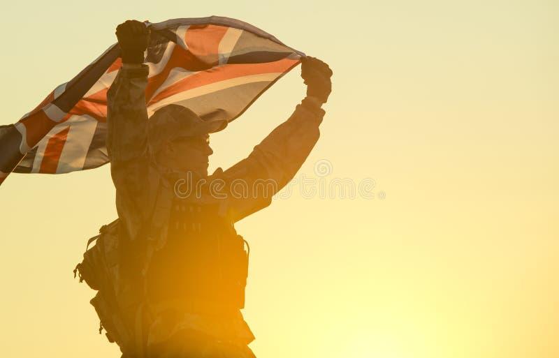 Soldado británico con la bandera BRITÁNICA imagen de archivo libre de regalías